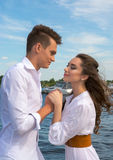 Guy holding hands a girl on a wooden pier near the Stock Photos