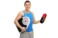 Guy holding a huge pill and a weight scale Royalty Free Stock Photo