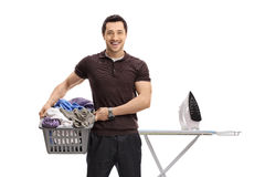 Guy holding a laundry basket in front of ironing board Stock Photos