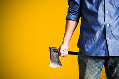 A guy holding old rusty axe, close up front view, on yellow background with copy space Royalty Free Stock Photos