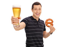 Guy holding a pretzel and a beer Stock Image