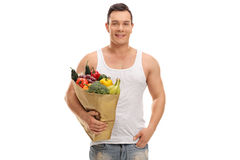 Guy holding a shopping bag full of groceries. Smiling guy holding a shopping bag full of groceries isolated on white background Stock Images