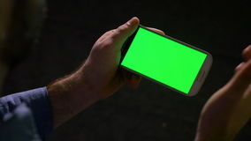 Guy holding showing and pointing at a smart phone with green screen in hands stock footage