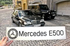 March 31, 2015, Kiev. The guy holding the sign `Mercedes E500` on the background of Mercedes royalty free stock image