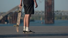 Guy holding skateboard. Skateboarder wears shorts. Developing talent takes time. From simple to difficult stock footage