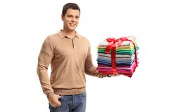 Guy holding a stack of ironed and packed clothes wrapped with re Stock Images