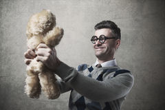 Guy holding a teddy bear. Childish funny guy with glasses holding a cute teddy bear Royalty Free Stock Photo