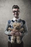 Guy holding a teddy bear. Childish funny guy with glasses holding a cute teddy bear Stock Image