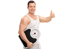 Guy holding a weight scale and giving thumb up royalty free stock photography