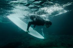 Guy holding a surf board dive under the wave. Guy holding a white surf board dive under the wave of clear blue sea water ready to surfing stock image