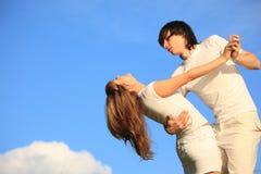 Guy holds girl against sky Royalty Free Stock Image