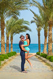 The guy holds the girl on hands on a beach with palm trees.  Royalty Free Stock Photo