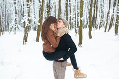 Guy holds the girl on hands in snow park Stock Photo