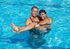 Guy holds a girl on hands while standing in the pool Royalty Free Stock Image