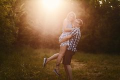 Guy holds a girl on hands in sunset light stock photography