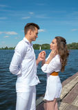 Guy holds the girls hand on a wooden pier near the Royalty Free Stock Images
