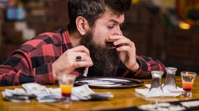 Guy holds rolled banknote, defocused background. Man with busy face. Alone at bar counter, sniffing drug. Hipster with beard sniffs cocaine, drug. Get high Royalty Free Stock Image