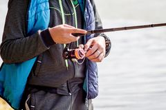 The guy holds spinning while fishing_ stock photo