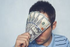 The guy holds up a one 500 dollars bill before my eyes. See through money. hiding behind money. cover his eyes for a bribe Royalty Free Stock Photo