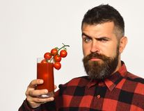 Guy with homegrown harvest. Farmer with confused face offers fresh juice made of tomatoes. Guy with homegrown harvest. Farmer with confused face offers fresh royalty free stock photos