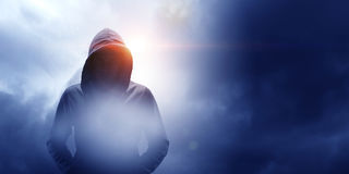 Guy in hoody. Mixed media. Criminal man wearing hoody against dark background. Mixed media Stock Image