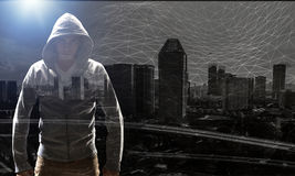Guy in hoody. Mixed media. Faceless man in hood against modern city background Stock Photo