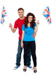 Guy hugging his girlfriend both holding UK flag Stock Images