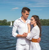 Guy hugs a girl near the water. Royalty Free Stock Photo