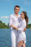 Guy hugs a girl near the water. Royalty Free Stock Image