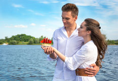 Guy hugs a girl near the water and holding her hand. Girl holdin Royalty Free Stock Images