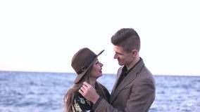 Guy hugs a girl by the sea stock video footage