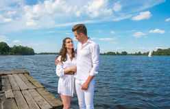 Guy hugs a girl on a wooden pier near the water. Royalty Free Stock Image