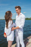 Guy hugs a girl on a wooden pier near the water. Stock Photo