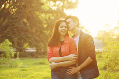 Guy hugs his girlfriend from behind. Date of teenagers. The guy hugs her friend from behind. He whispers in her ear tenderness. Human faces are emotions. Sunset Stock Photos