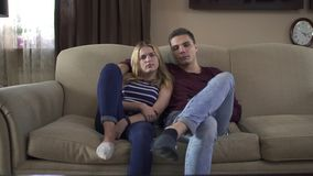 Guy hugs his girlfriend and watch tv with her at home. Young couple watching tv at home sitting at sofa in living room. People looking at camera like in tv set stock video