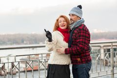 Guy hugs woman on bridge. Couple of aged people look to one way. Urban couple date on bridge. Woman shows to man the way royalty free stock photography