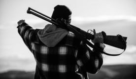 Guy hunter spend leisure hunting. Hunting masculine hobby leisure concept. Brutality and masculinity. Hunter carry rifle. Gun on shoulder rear view. Man brutal royalty free stock photo