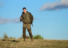 Guy hunting nature environment. Masculine hobby activity. Hunting weapon gun or rifle. Man hunter carry rifle blue sky. Background. Experience and practice stock photos