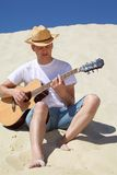 Guy In Straw Hat Plays Guitar Sitting On Sand Stock Images
