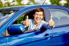 Guy inside car showing thumbs up. Close up of young happy hispanic man wearing glasses showing thumb up hand gesture with both hands and laughing through car Royalty Free Stock Images