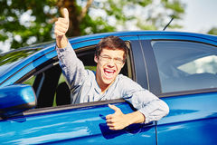Guy inside car showing thumbs up. Close up of young hispanic man wearing glasses showing thumb up hand gesture and happy screaming through car window - driving Royalty Free Stock Photos