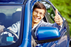 Guy inside car showing thumbs up. Young happy hispanic man wearing glasses sitting inside car, holding steering wheel,  showing thumb up hand gesture through car Royalty Free Stock Photo