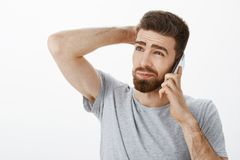 Guy intense, awkward trying say no during phone call. Unsure hesitating handsome boyfriend with beard and sick eyebrows. Scratching back of head gazing up royalty free stock photography