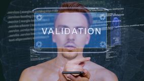 Guy interacts HUD hologram Validation. Young man interacts with a conceptual HUD hologram with text Validation. Guy with future technology mobile screen on stock footage
