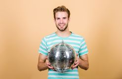 Guy inviting you at party. Thousand tiny mirrors reflecting lights creating disco atmosphere. How about party. Cheerful. Dj man. Handsome man hold disco ball stock image