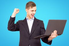 Guy in a jacket and blue shirt with a laptop rejoices, isolated on a blue background royalty free stock photos