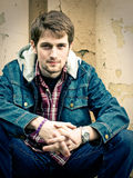 Guy in jeans clothes. Young man wearing jeans clothes sits in front of the cracked wall Stock Photos