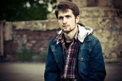 Guy in jeans clothes. Young man wearing jeans clothes in front of the cracked ruined wall Royalty Free Stock Photos