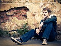 Guy in jeans clothes. Young man wearing jeans clothes sits on the ground in front of the cracked ruined wall Royalty Free Stock Photos