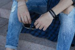 The guy in jeans is holding glasses. man`s hand holds glasses. Hipster men`s hand holds glasses Royalty Free Stock Photos